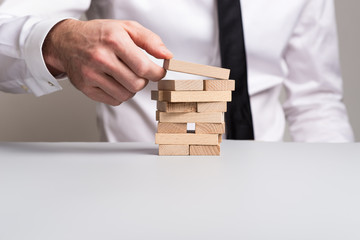 Front view of businessman building a tower of wooden pegs