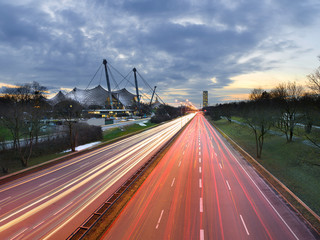 Light trails of cars driving/commuting past modern architecture in a city - Munich, Germany