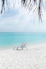 Sun chair on sandy beach at tropical vacation,