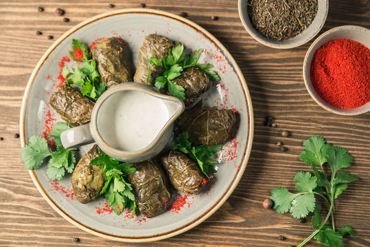 """Traditional Georgian and Armenian cuisine. The dish """"Dolma"""". Cabbage rolls of grape leaves with rice and minced meat. Copy space, selective focus"""