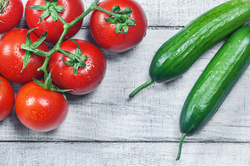 ripe fresh grape tomatoes and cucumbers on white wooden background. Cherry tomato and cucumber vegetable salad concept