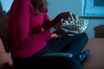 Woman watching tv at home and eating popcorn