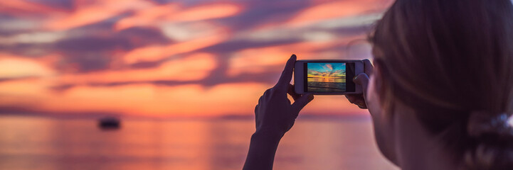 Young asia woman selfie with mobile phone on a beach at sunset in summer, Phuket, Thailand BANNER, LONG FORMAT