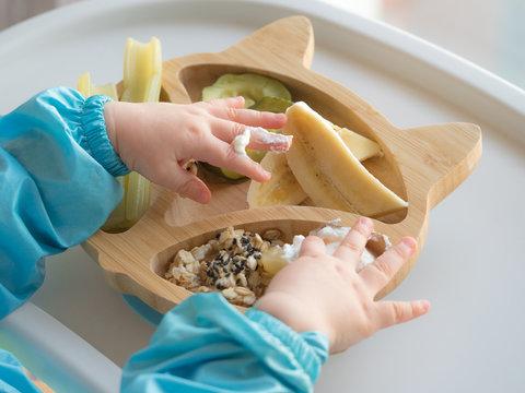 Baby eating by hands, Baby eating organic bio vegetables with BLW method, baby led weaning. Happy vegetarian kid eating lunch. Toddler eat himself, self-feeding. infant baby eating. Greek Yogurt.