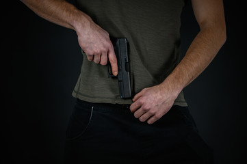 Man try to hide his pistol under his pants