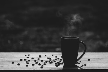 Hot coffee cup with organic coffee beans on the wooden table and blurred background with copy space