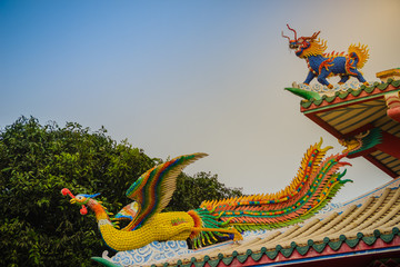 Beautiful Chinese dragon-headed unicorn and Chinese phoenix statues on the roof in Chinese temple with dramatic sky background.