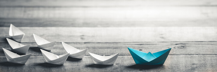 Blue Paper Boat Leading A Fleet Of Small White Boats On Wooden Table With Vintage Effect - Leadership Concept