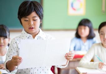 授業中に作文を読む小学生の男の子