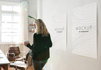 Woman in a working space with poster design mockups Wall mural