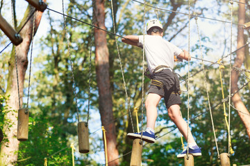 Cheerful cute young boy in white t shirt and white helmet in adventure rope park at sunny summer day. Active lifestyle, sport, holidays for children