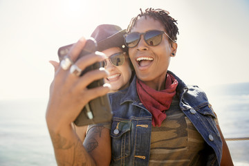 Two smiling women taking a selfie near the beach