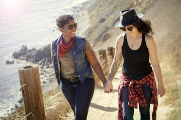 Couple holding hands and laughing on a hike near the ocean