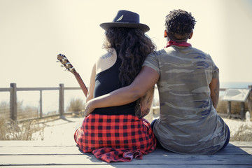 Rear view of couple sitting with guitar outdoors