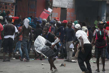 People loot an electronics store during anti-government protests in Port-au-Prince