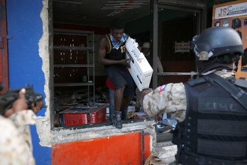 Police officers stop a looter during anti-government protests in Port-au-Prince