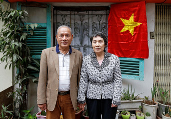 Former Vietnamese chemical student Pham Ngoc Canh who studied in North Korea and his North Korean wife Ri Yong Hui stand in front of their house while posing for a photo in Hanoi