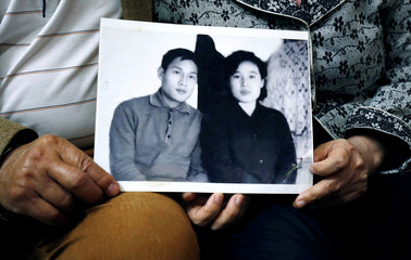 Former Vietnamese chemical student Pham Ngoc Canh who studied in North Korea and his North Korean wife Ri Yong Hui hold their first photo together which was taken in Spring 1971, at their house in Hanoi