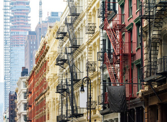 Old historic buildings along Greene Street in SoHo Manhattan contrast against the modern tower in the background Manhattan skyline in New York City