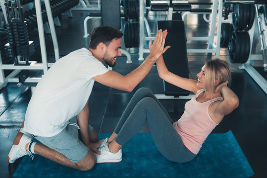 Attractive fitness couple love giving high five together after workout in fitness gym., Portrait of man and woman sporty are working out training together., Couple fitness and healthy concept.