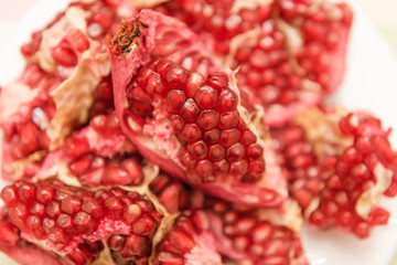 Fototapeta Pomegranate on a white background. Natural fruit. Red fruit. Pomegranate on the table.
