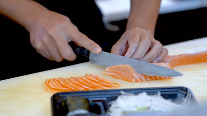 The chef is cutting the salmon fillet and arranging it into a beautiful tray.