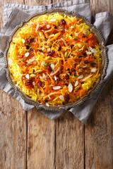 Javaher Polow (jeweled rice) is a traditional Persian rice dish closeup on a plate. Vertical top view