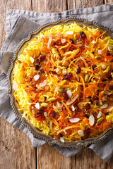 Saffron pilaf with dried fruits, carrots, orange zest, spices and nuts closeup on a plate. Vertical top view