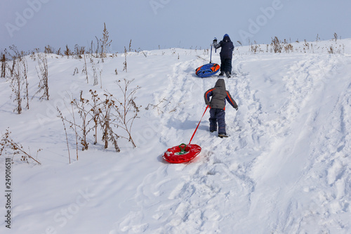 4f8727ff9fd8e0 child climb the hill with a tube for descent. Children ride in the winter  with