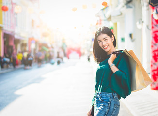 Asian women are addicted to shopping or shopaholic shopping in the old town with colorful paper shopping bags during the discount season with copy space and blur city or tourist background, Soft tone.