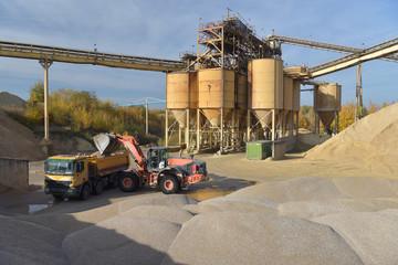 Radlader belädt LKW mit Sand in einem Kieswerk // Wheel loader loads truck with sand in a gravel plant