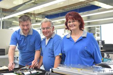 Gruppe Arbeiter in einer Fabrik zur Montage von Elektronik - Portrait glückliche Menschen am Arbeitsplatz // Group of workers in a factory for the assembly of electronics - Portrait of happy people at
