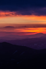 Beautifully colored sky at dusk, with mountains layers