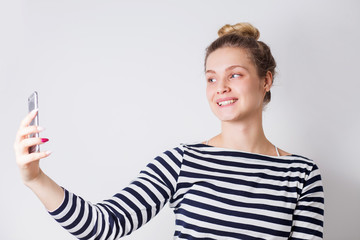Studio portrait of beautiful woman smiling with white teeth and making selfie, photographing herself over white background