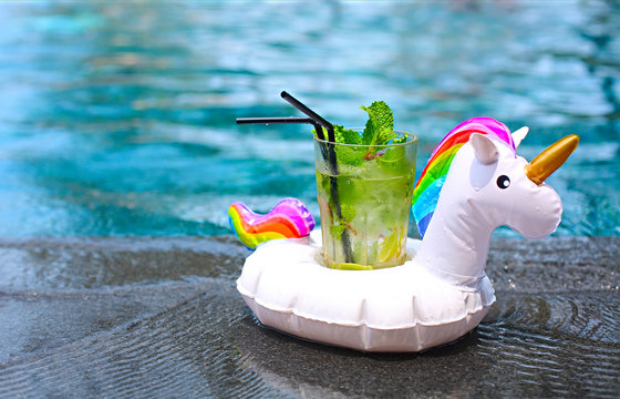 Mojito cocktail at the edge of a resort pool in inflatable unicorn. Concept of luxury vacation