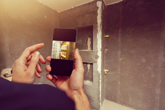Mobile device with man hands taking picture in tiled bathroom