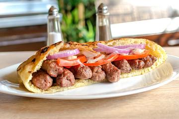 Delicious Serbian beef kebab sandwich in pita bread with fresh salad ingredients