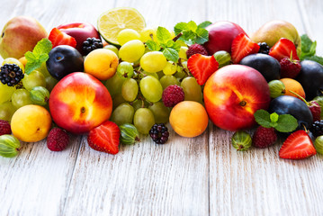 Fresh summer fruits and berries on a white wooden table