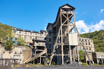 Abandoned coal factory. Industrial rusted machinery. Polluted landscape. Energy