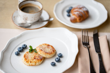 Cheesecake, fresh blueberry and cappuccino. Cottage cheese pancakes or curd fritters on white plate. Healthy and diet breakfast at sunrise