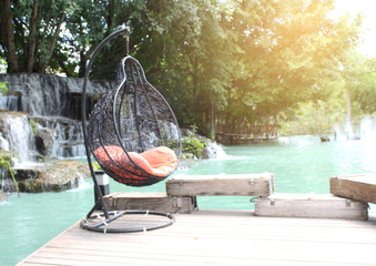 rattan swing chair on waterfront