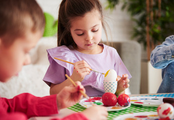 Focused girl painting easter eggs