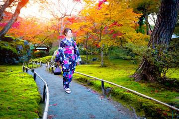 Asian woman wearing japanese traditional kimono in autumn garden.