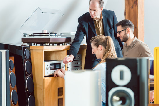 Couple testing a Hi-Fi system in the store with the salesman explaining