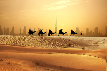 Spoed Fotobehang Dubai Camel caravan on sand dunes on Arabian desert with Dubai skyline at sunset
