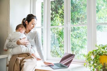 パソコンを見るママと赤ちゃん