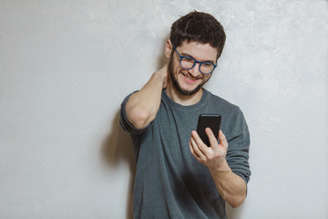 Portrait of young man using smartphone, over white textured background.