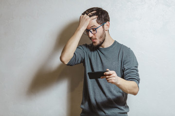 Portrait of young man playing video games on smartphone, over white textured background.