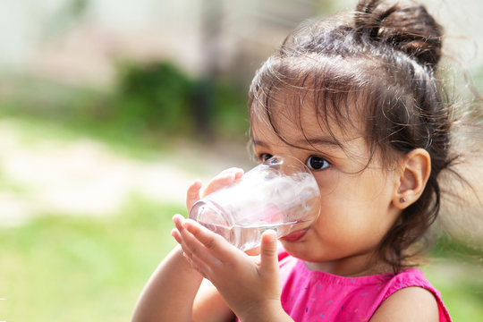 Cute child girl drinking clear water outdoors. Pure water