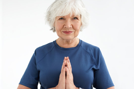 Calm beautiful elderly woman with short gray hair and wrinkles holding hands in namaste during yoga practice. Athletic peaceful mature female on retirement wearing t-shirt meditating indoors